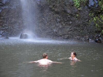 Becky Dean and her son swimming in a pool with a waterfall in the background