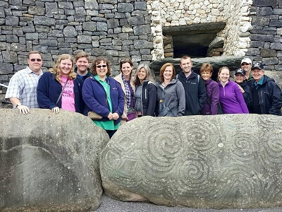 Tom & Becky Dean and several Book Nation team members at the Newgrange tomb in Ireland - standing behind the very large entrance kerbstone with megalithic art engraved on it and the tomb in the background.