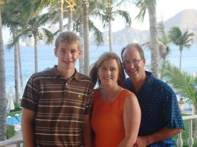 Tom & Becky Dean with their son in the Mexican Riviera - palm trees and ocean beyond