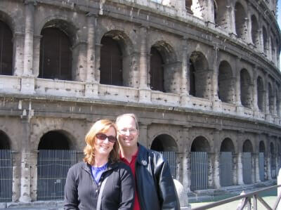 Tom & Becky Dean standing in front of the Coliseum in Rome