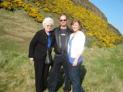Tom & Becky Dean with Becky's mom in Scotland - a hill of green and yellow flower beyond