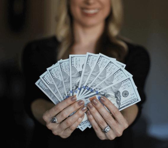 woman holding several 100 dollar bills